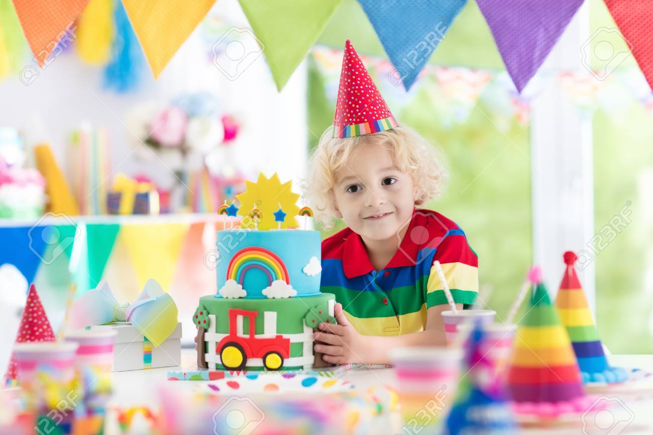 Kids Birthday Party Child Blowing Out Candles On Colorful Cake Decorated Home With Rainbow