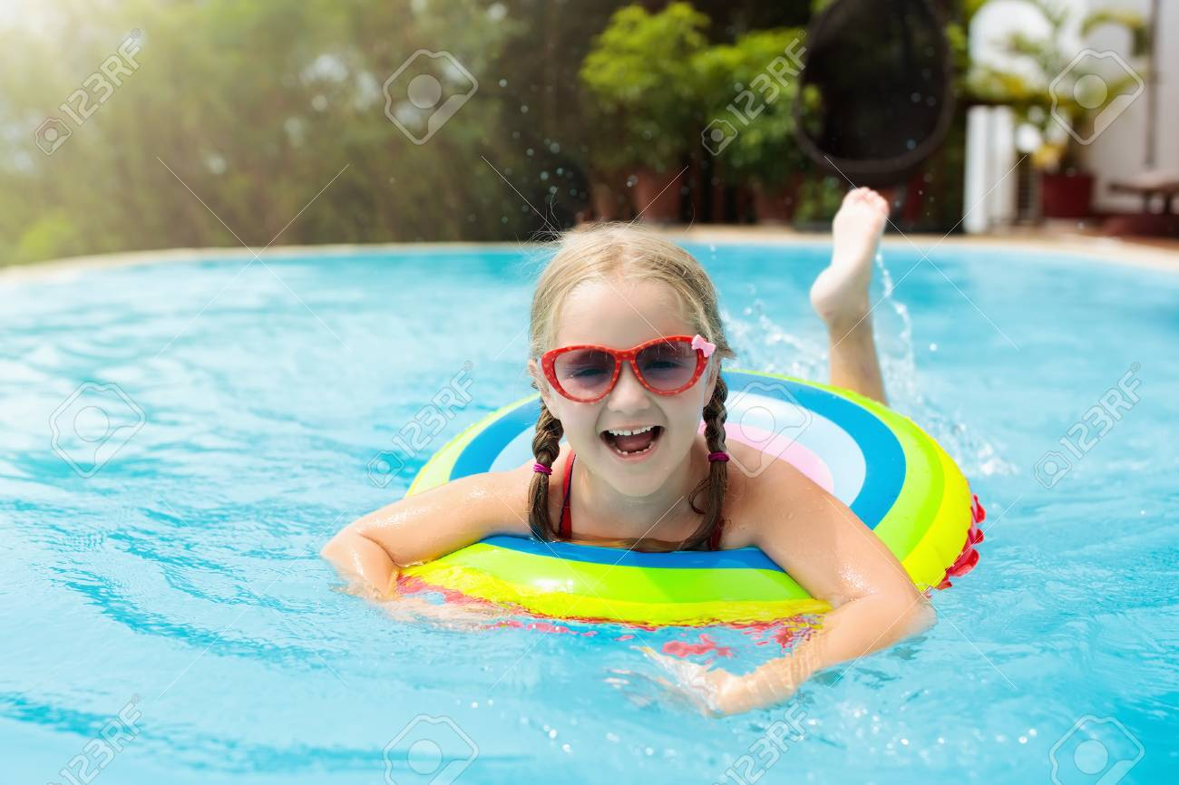 2737decff7 Child with goggles in swimming pool. Little girl learning to swim and dive  in outdoor