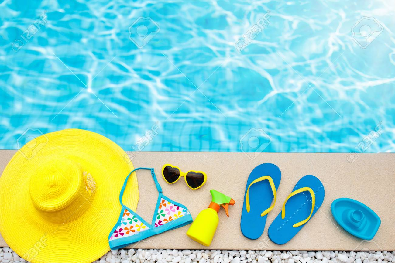Swimming pool accessories flat lay. Top view of beach items on..