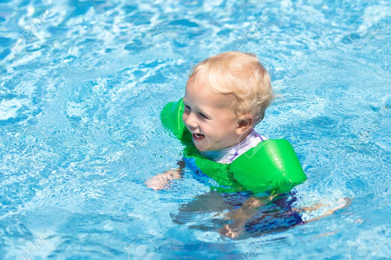 7c3a86a469d Baby with inflatable armbands in swimming pool. Little boy learning to swim  in outdoor pool