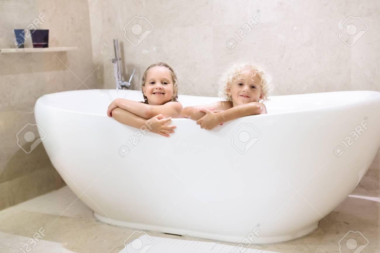 Kids Taking Bubble Bath. Children Bathing In Freestanding Bathtub ...
