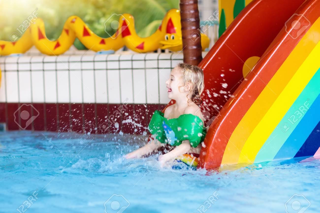 Child On Swimming Pool Slide Kid Having Fun Sliding In Water Amusement Park Kids