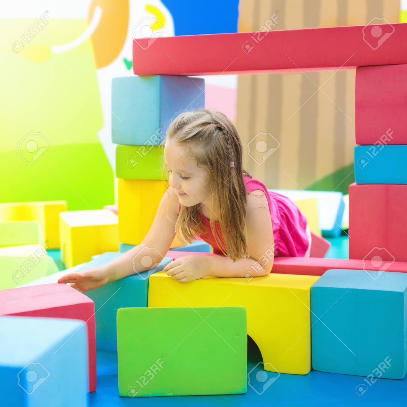 Child playing with colorful construction toy blocks. Educational..