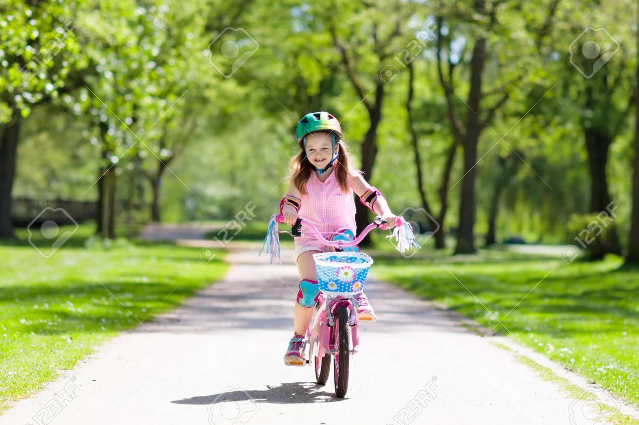 Child riding a bike in summer park  Little girl learning to ride