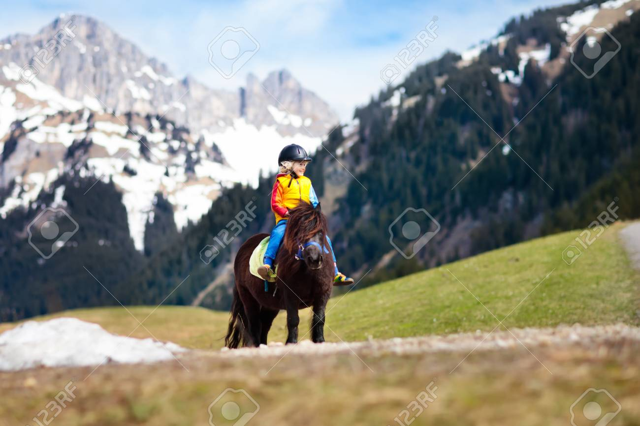 Kids Riding Pony In The Alps Mountains Family Spring Vacation On Horse Ranch Austria