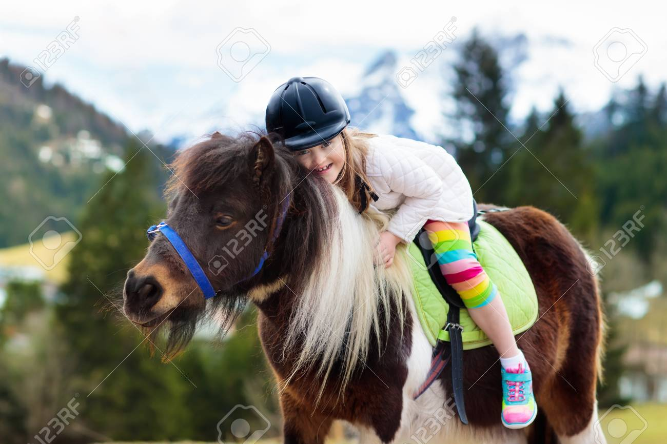 Kids Riding Pony In The Alps Mountains Family Spring Vacation Stock Photo Picture And Royalty Free Image Image 100107337