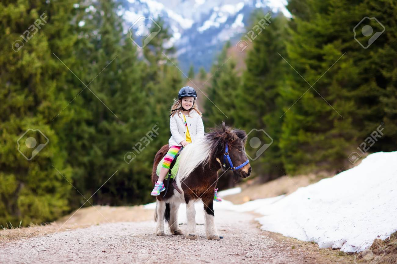 Kids riding pony in the Alps mountains  Family spring vacation