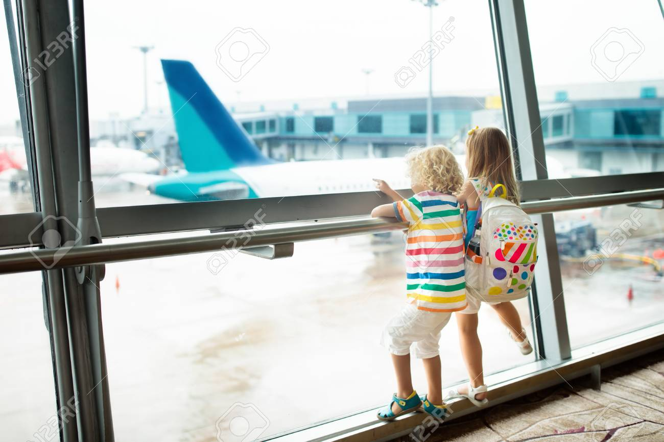 Kids at airport. Children look at airplane. Traveling and flying with child. Family at departure gate. Vacation and travel with young kid. Boy and baby before flight in terminal. Kids fly a plane. - 101489183