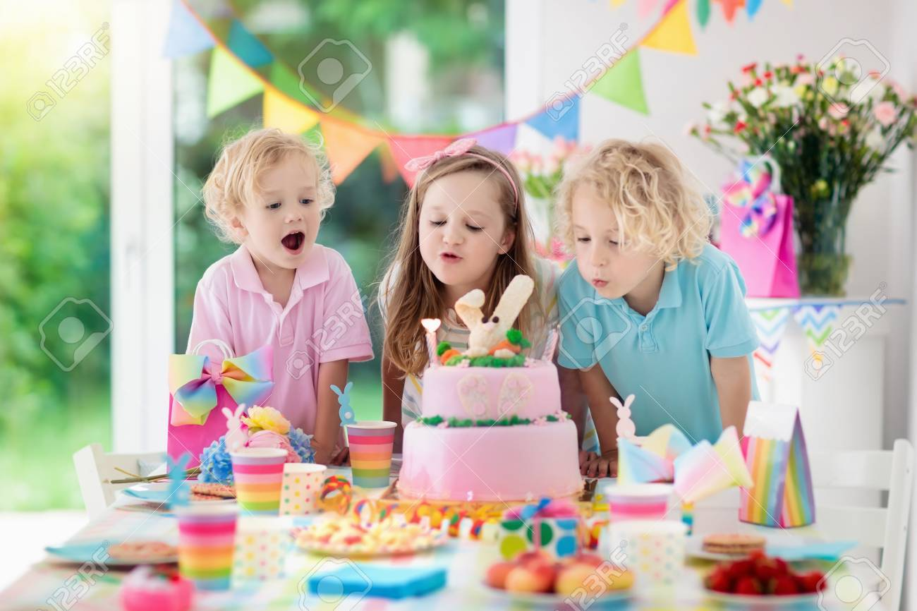 Kids birthday party. Children blow out candles on pink bunny cake. Pastel rainbow decoration and table setting for kids event, banner and flag. - 102743767
