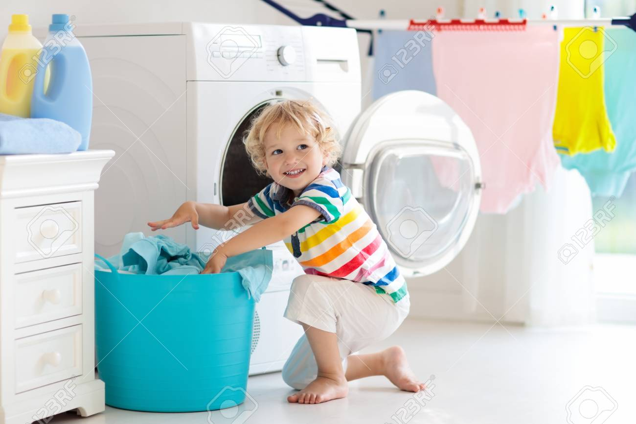 child laudry room Child in a laundry room with washing machine or tumble dryer...