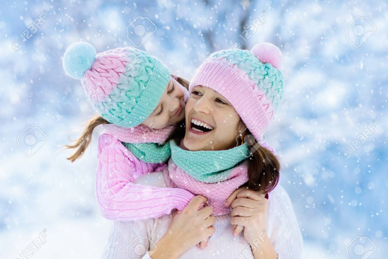 Mother and child in knitted winter hats play in snow on family Christmas  vacation. Handmade e0a3a83c35c2