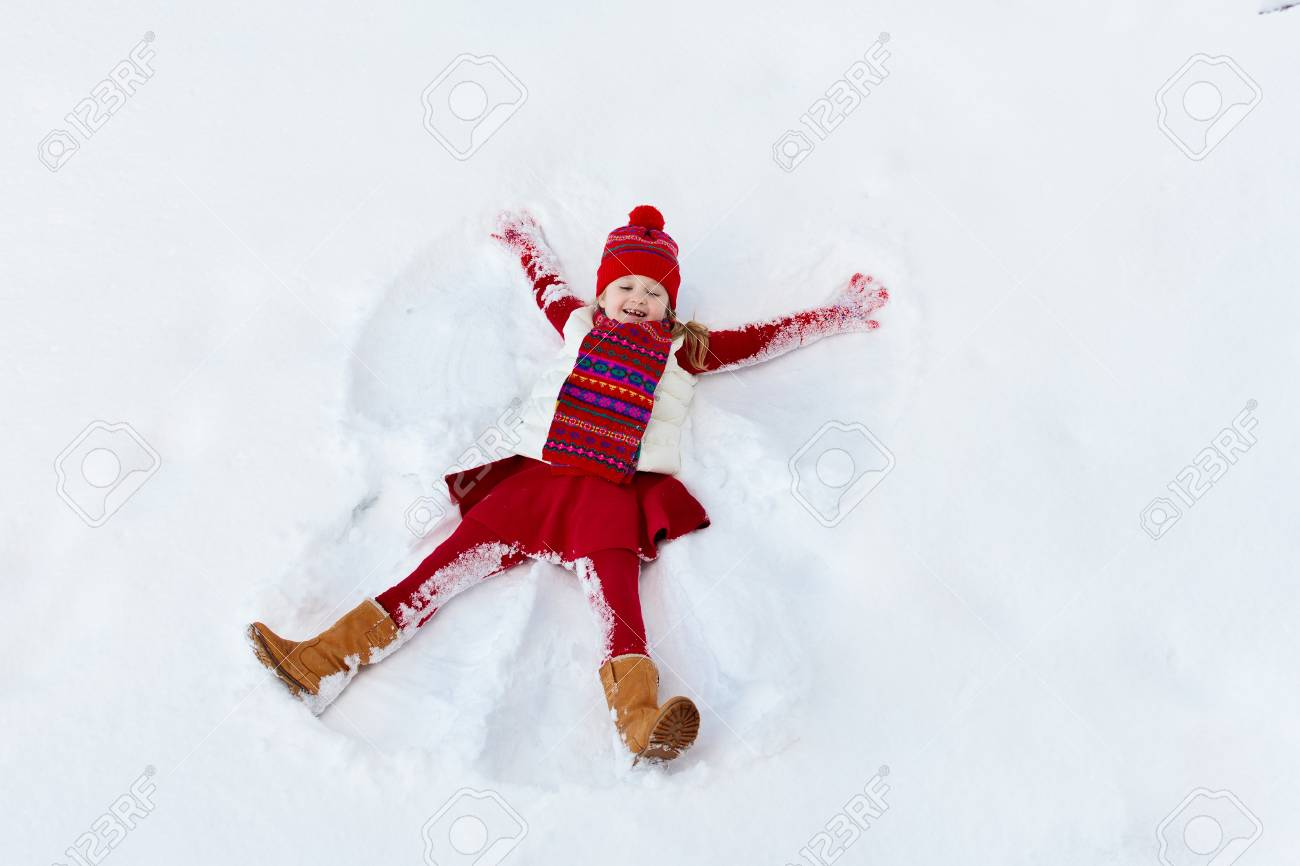 83ad2cf895 Child making snow angel on sunny winter morning. Kids winter outdoor fun.  Family Christmas