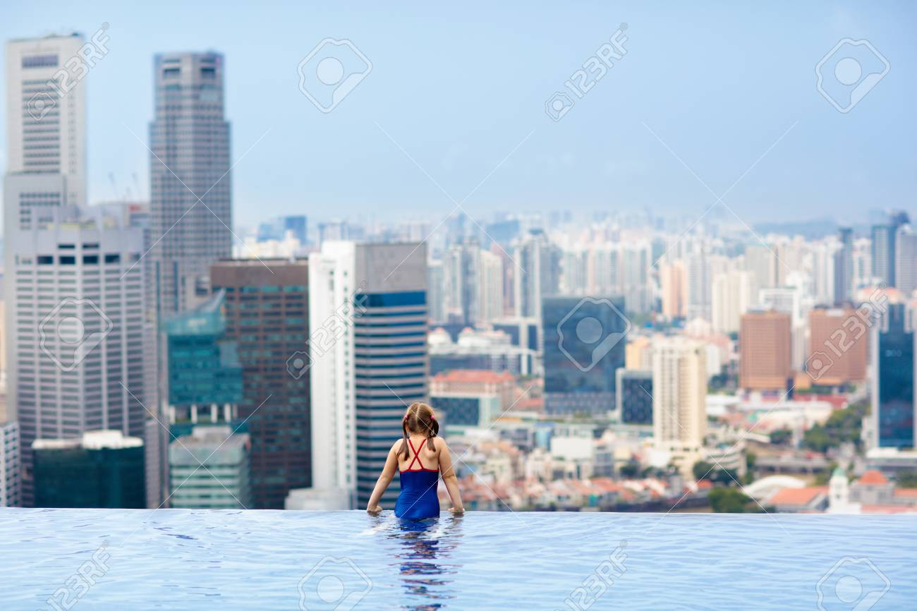 Children Swimming In Roof Top Outdoor Pool On Family Vacation