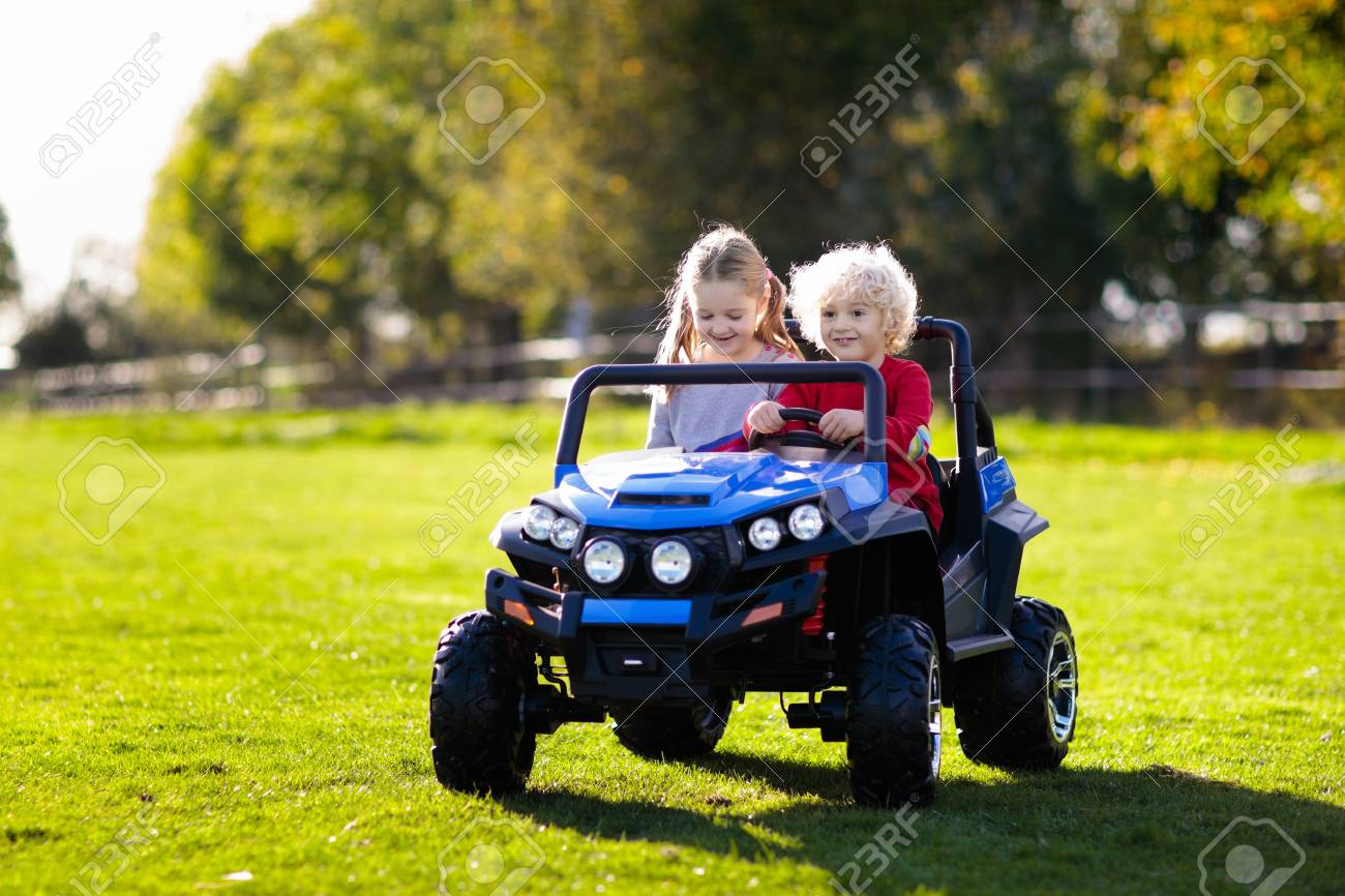 Kids driving electric toy car in summer park. Outdoor toys. Children in battery power vehicle. Little boy and girl riding toy truck in the garden. Family playing in the backyard. - 116565280