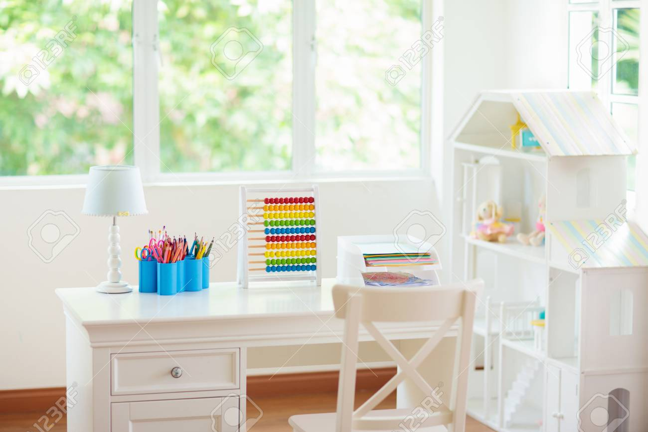 Kids bedroom with wooden desk and doll house. White sunny room..