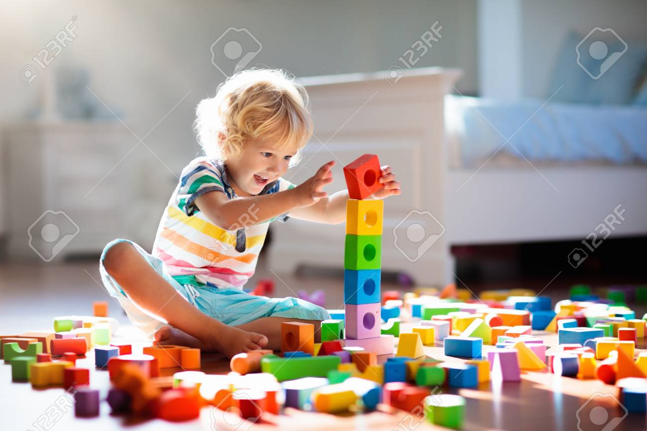 Child playing with colorful toy blocks. Kids play. Little boy building tower of block toys sitting on dark floor in sunny white bedroom. Educational game for baby and toddler. Children build toy house - 116565953