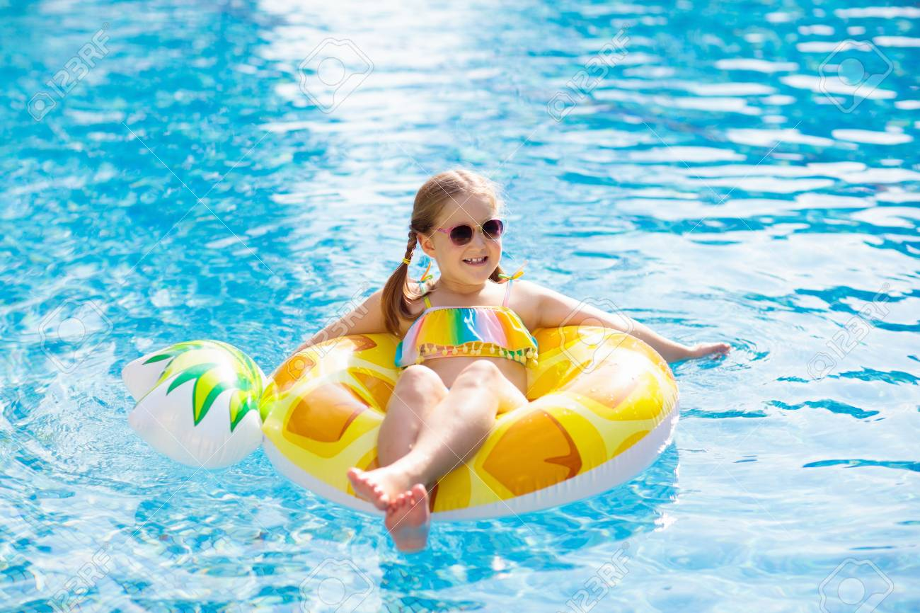 38851c973e Child with inflatable pineapple toy ring float in swimming pool. Little  girl learning to swim and dive in outdoor pool of tropical resort.