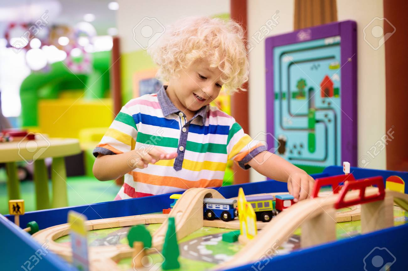 Kids Play Toy Railroad Little Blond Curly Boy With Wooden Trains