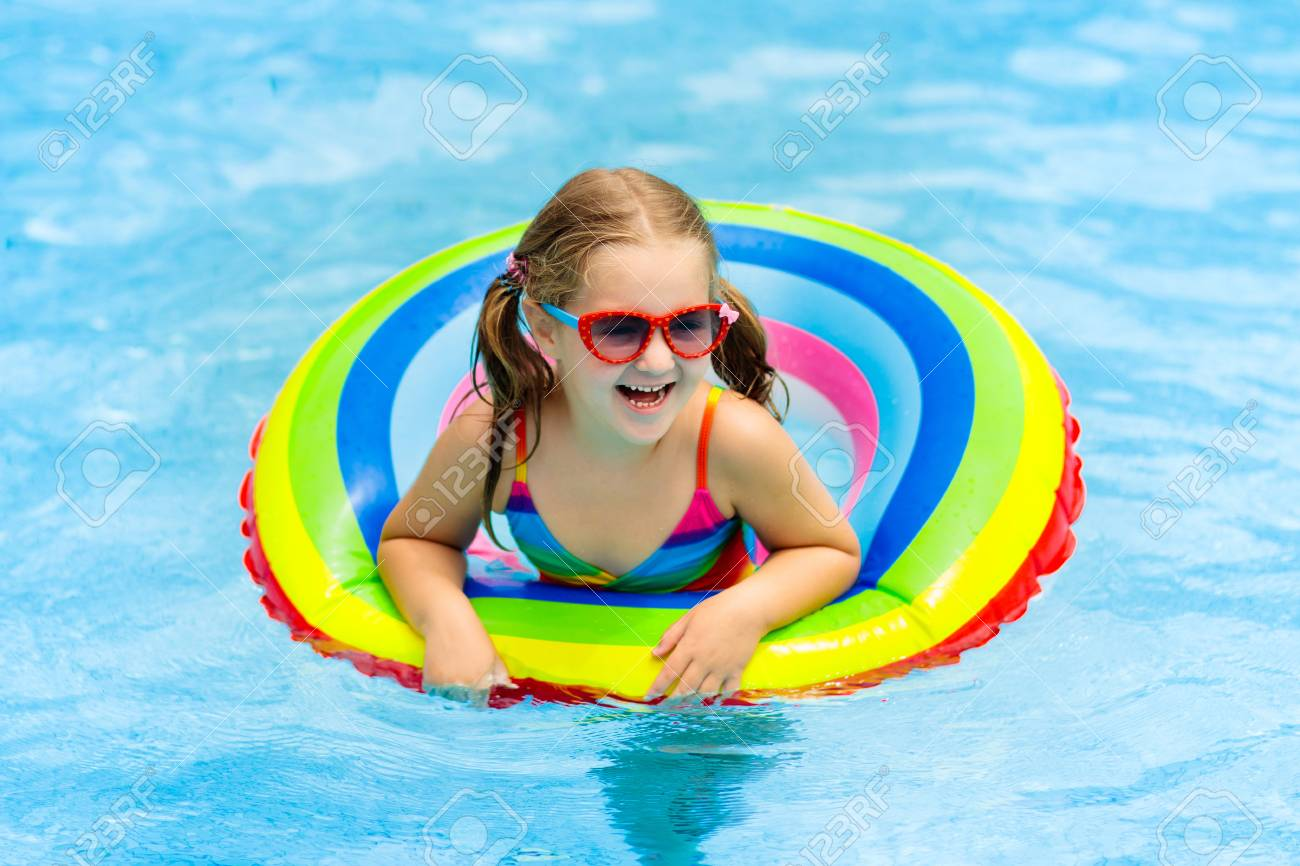 Child in swimming pool floating on toy ring. Kids swim. Colorful..