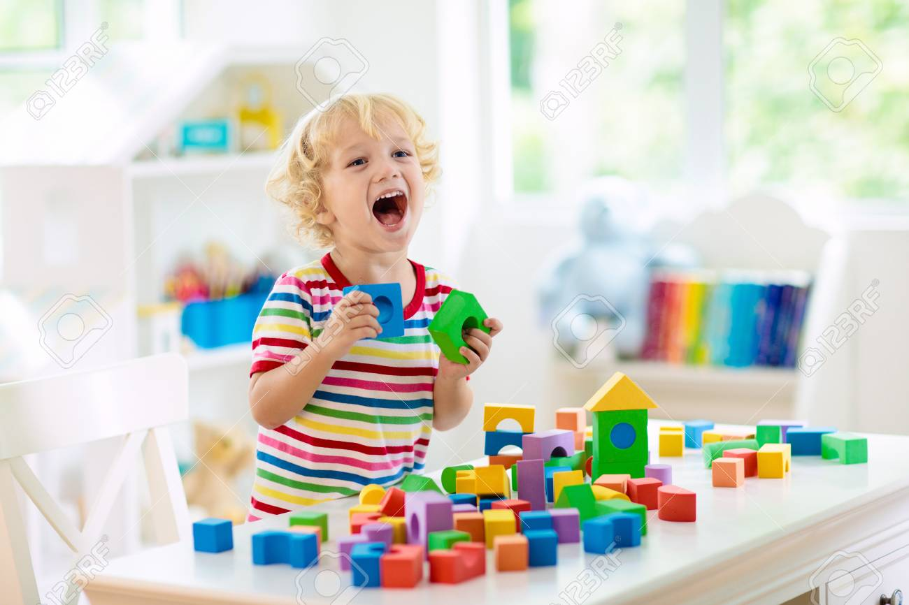 Kid playing with colorful toy blocks. Little boy building tower of block toys. Educational and creative toys and games for young children. Baby in white bedroom with rainbow bricks. Child at home. - 122316843