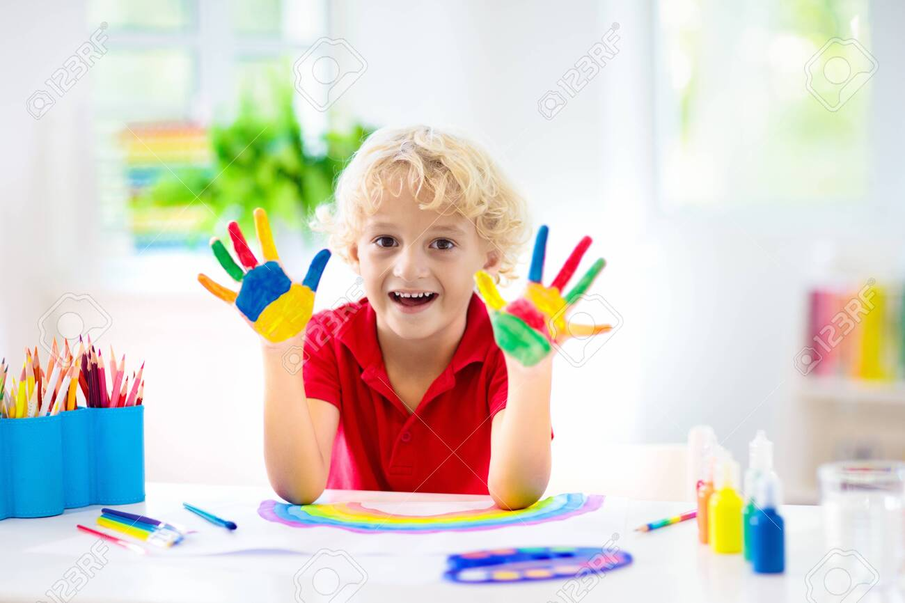 Kids paint. Child painting in white sunny study room. Little boy drawing rainbow. School kid doing art homework. Arts and crafts for kids. Paint on children hands. Creative little artist at work. - 123775506
