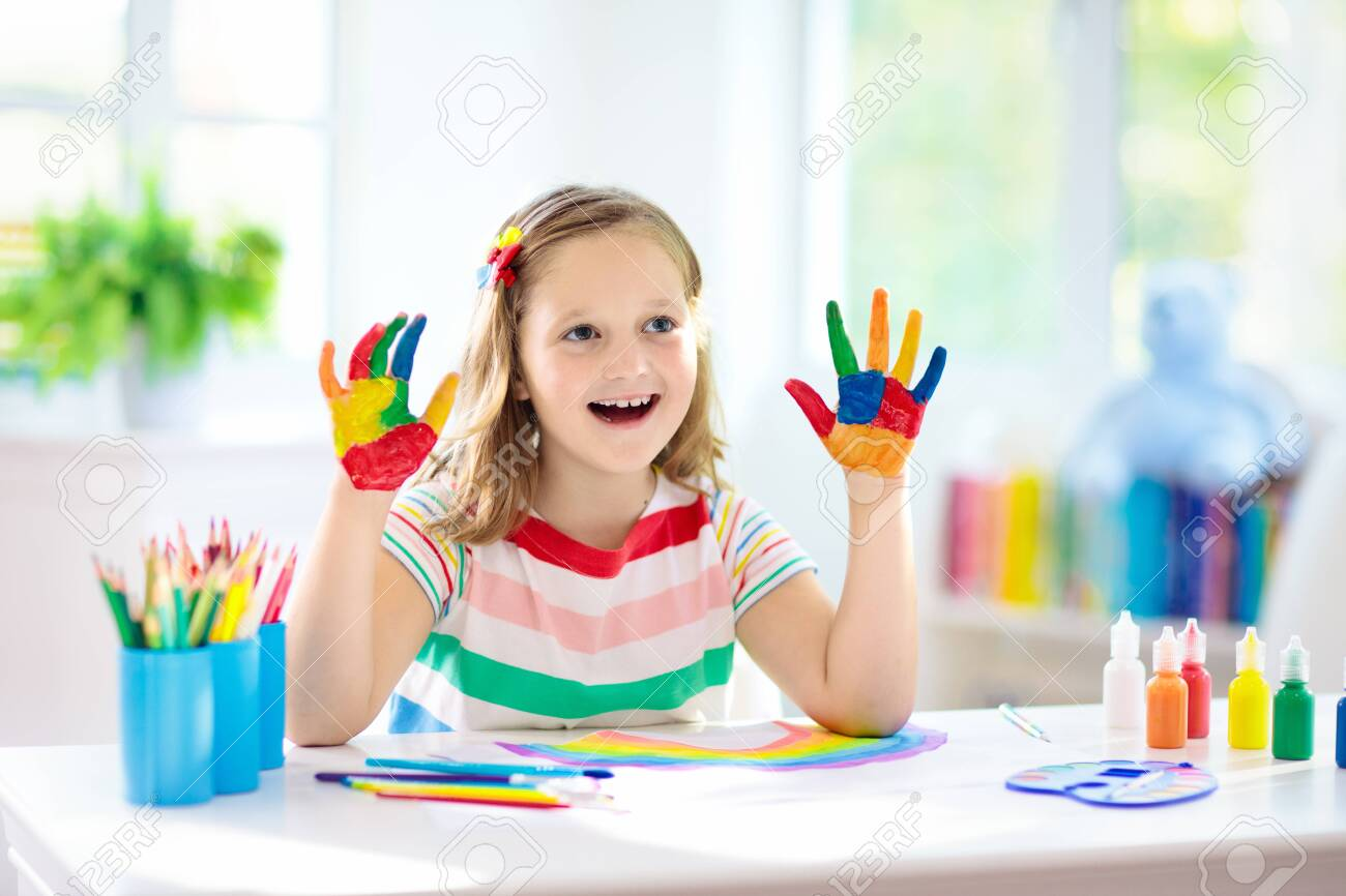 Kids paint. Child painting in white sunny study room. Little girl drawing rainbow. School kid doing art homework. Arts and crafts for kids. Paint on children hands. Creative little artist at work. - 123775522