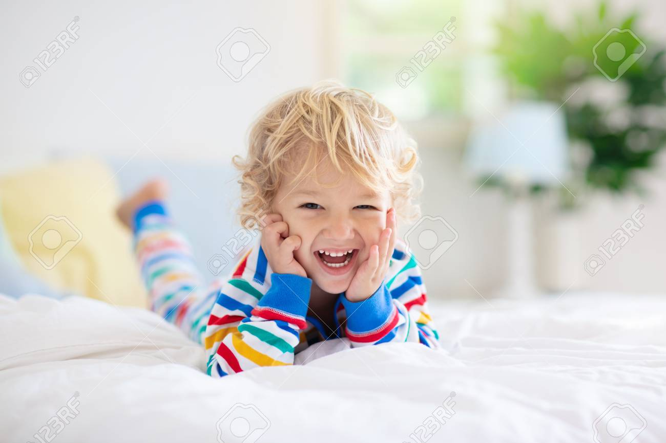 Child playing in bed in white sunny bedroom with window. Kids room and interior design. Baby boy at home. Bedding and textile for children nursery. Kid with toy and book. Nap and sleep time. - 123776408