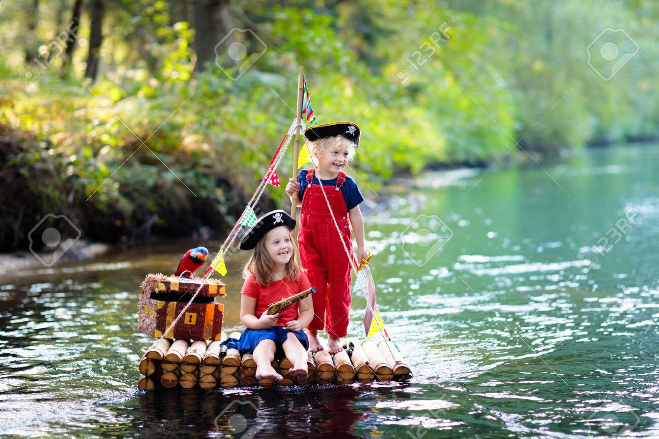 Kids dressed in pirate costumes and hats with treasure chest, spyglasses, and swords playing on wooden raft sailing in a river on hot summer day. Pirates role game for children. Water fun for family. - 123791972