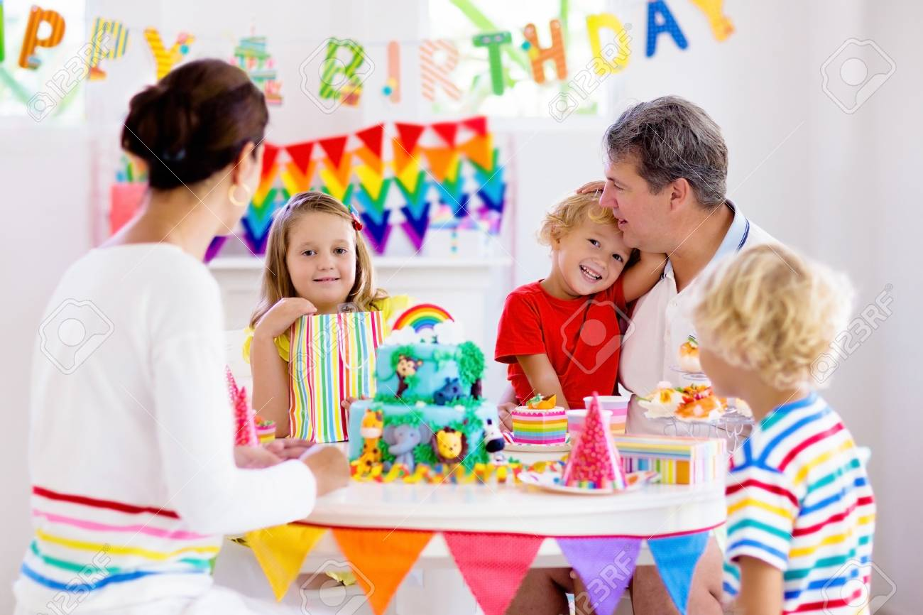 Kids birthday party. Child blowing candles on cake and opening presents on jungle theme celebration. Family celebrating at home. Mother, father, boy and girl open gifts, eat cakes. Sweets for children - 123791975