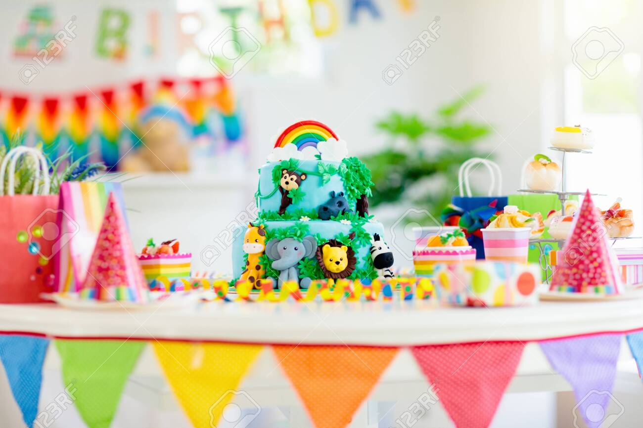 Cake for kids birthday celebration. Jungle animals theme children party. Decorated room for boy or girl kid birthday. Table setting with presents, gift boxes, confetti and sweets. Pastry for child - 126120638