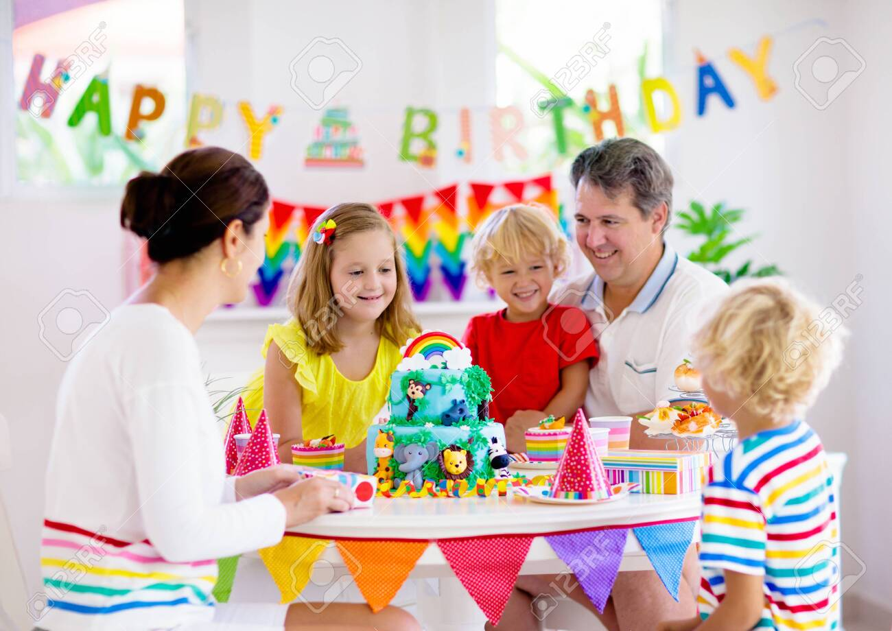 Kids birthday party. Child blowing candles on cake and opening presents on jungle theme celebration. Family celebrating at home. Mother, father, boy and girl open gifts, eat cakes. Sweets for children - 126111838