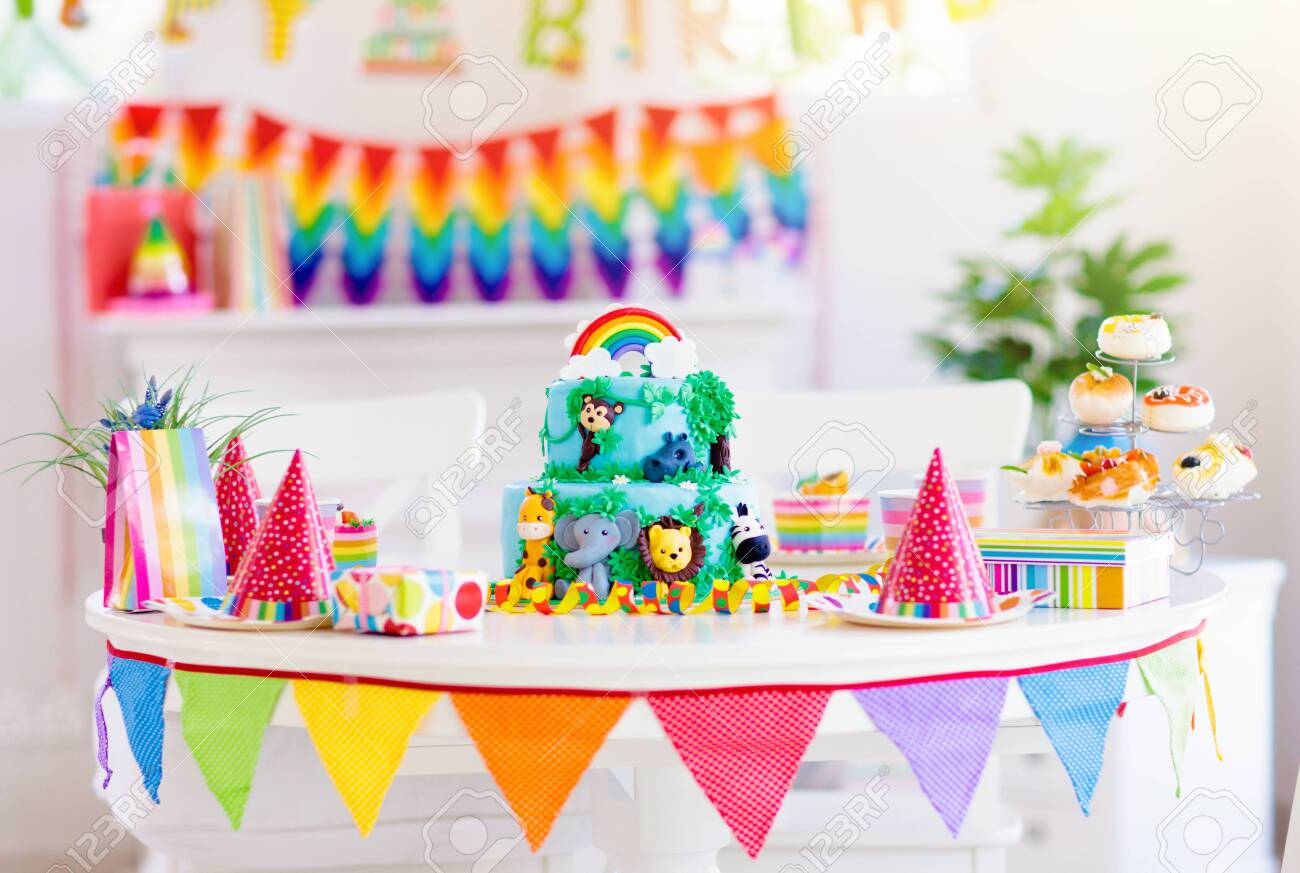 Kids birthday party. Child blowing candles on cake and opening presents on jungle theme celebration. Cakes dessert for children event. Boy and girl celebrate birthday. Gifts and sweets for kid. - 126120645