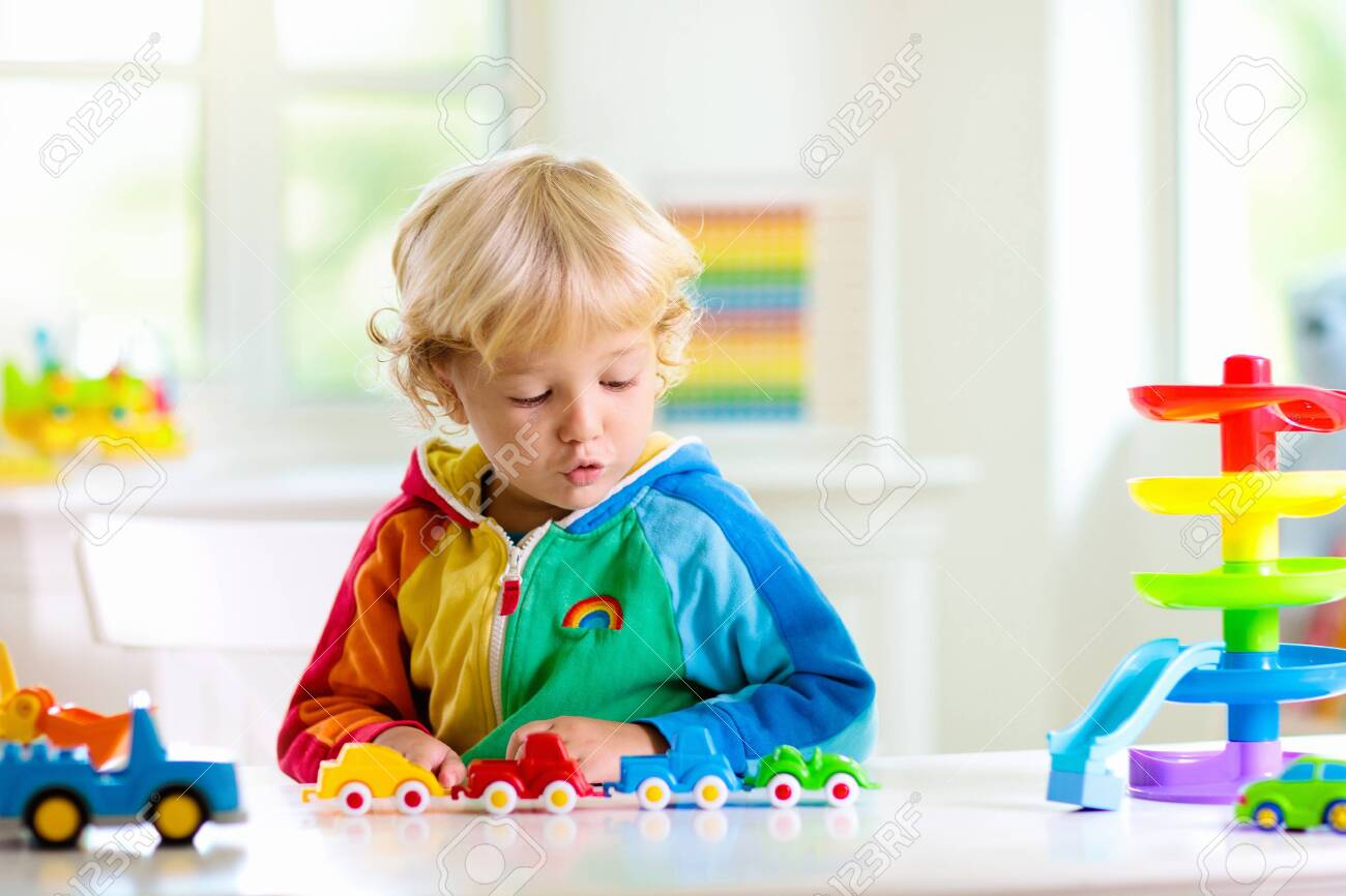 Little boy playing toy cars. Young kid with colorful educational vehicle and transport toys. Child driving car to rainbow parking garage. Kids at home or daycare. Kindergarten or preschool game. - 126191508