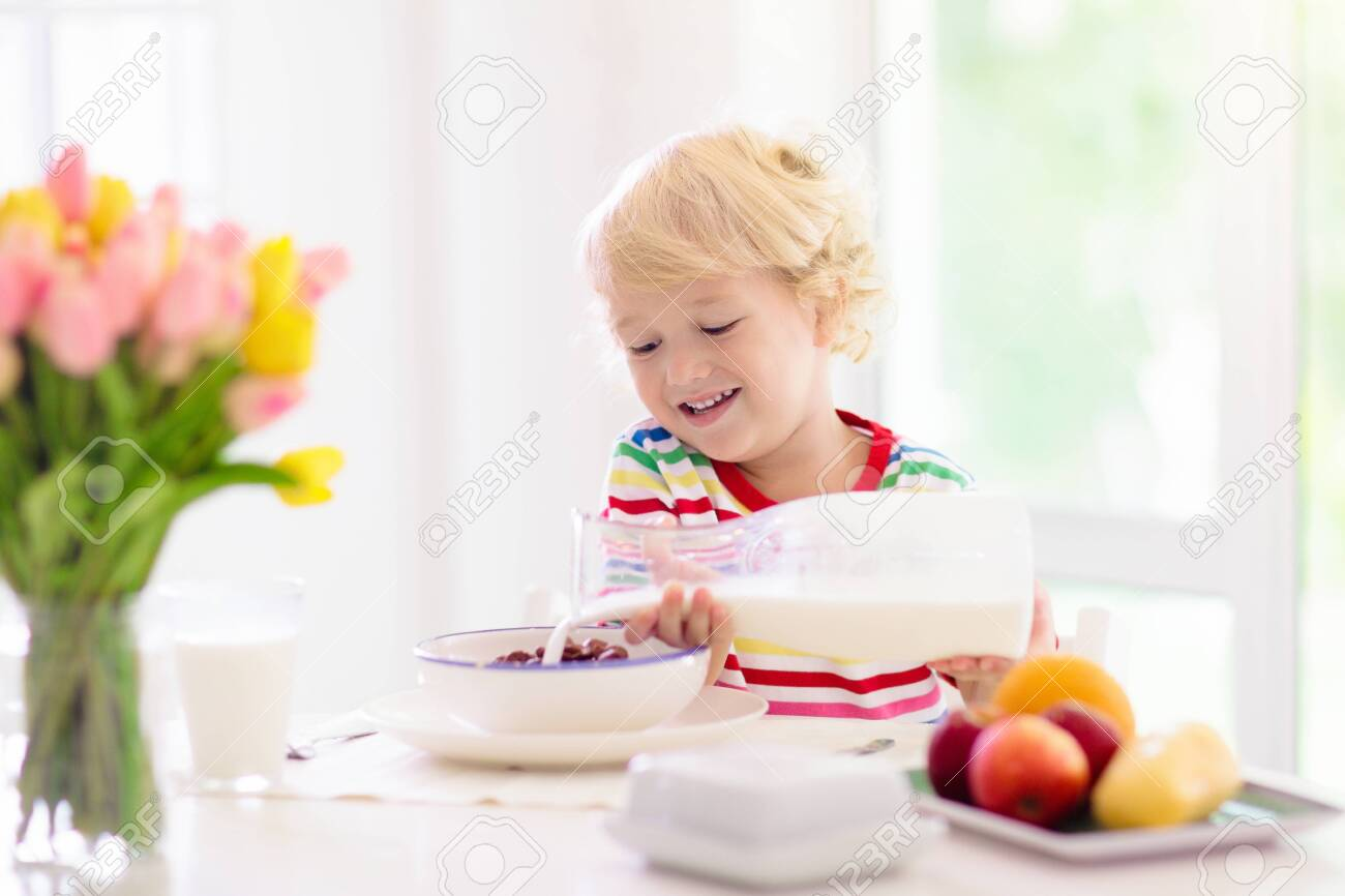 Child having breakfast. Kid drinking milk and eating cereal with fruit. Little boy at white dining table in kitchen at window. Kids eat on sunny morning. Healthy balanced nutrition for young kids. - 126187339