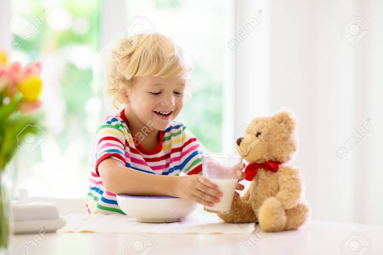 Child having breakfast. Kid feeding teddy bear toy, drinking milk and eating cereal with fruit. Little boy at white dining table in kitchen at window. Kids eat. Healthy nutrition for young kids. - 126187347