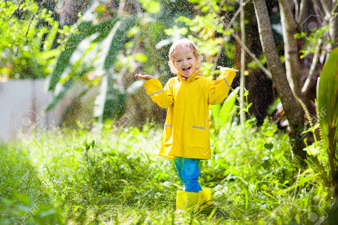 Child playing in the rain on sunny autumn day. Kid under heavy shower with yellow duck umbrella. Little boy with duckling waterproof shoes. Rubber wellies boots. Fall outdoor activity by rainy weather - 126187596
