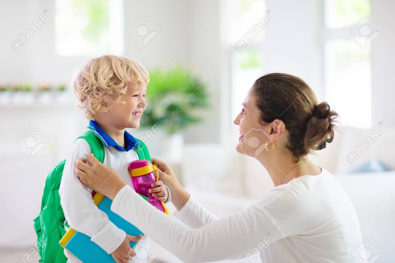 Child going back to school. Mother and kid getting ready for first school day after vacation. Little boy and mom going to kindergarten or preschool. Student packing books, apple and lunch in backpack. - 127843703