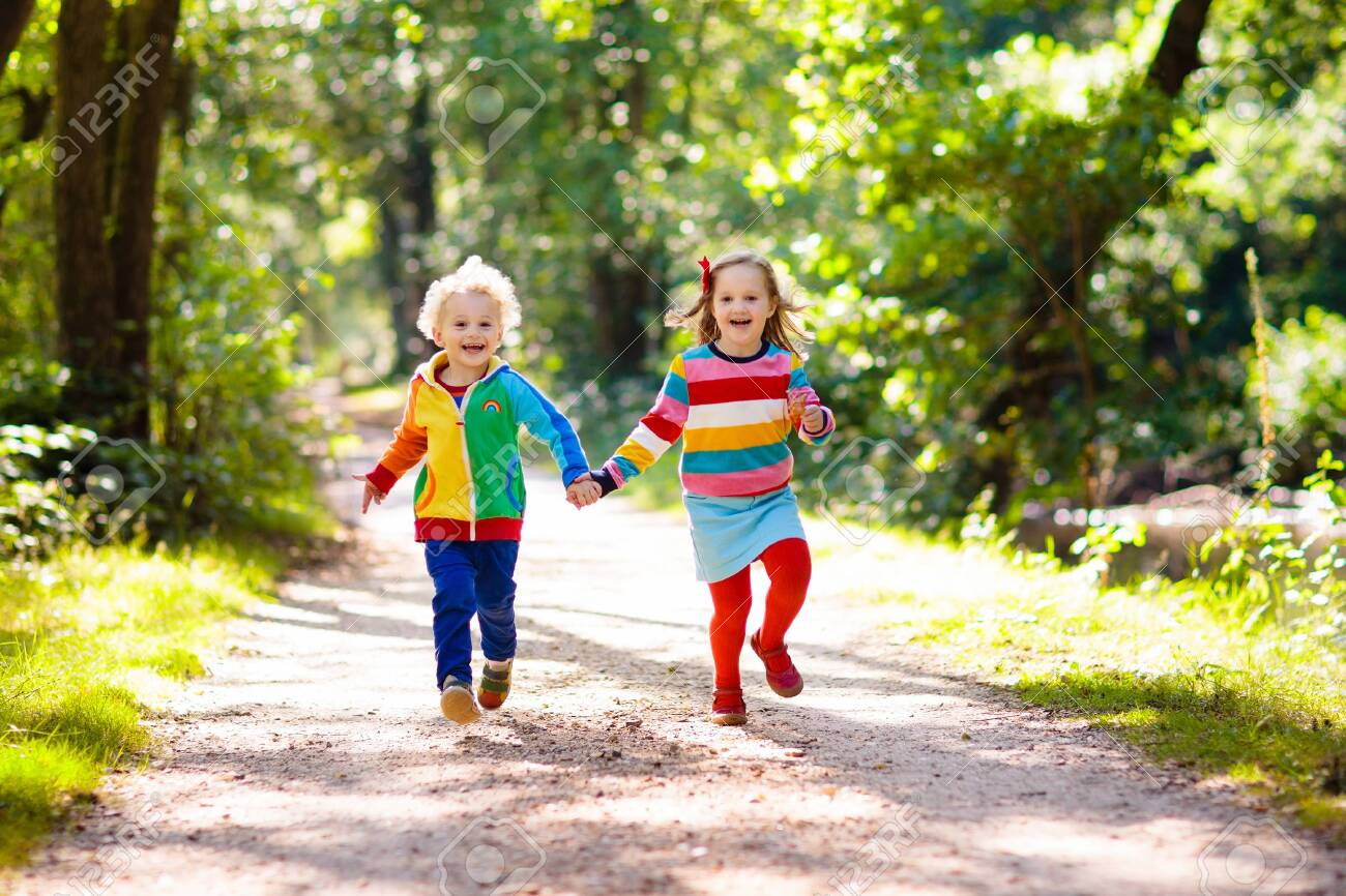 Children hiking in forest and mountains. Kids play outdoor in summer. Little boy and girl on hike trail in national park. Outdoor fun and healthy activity. - 128399395