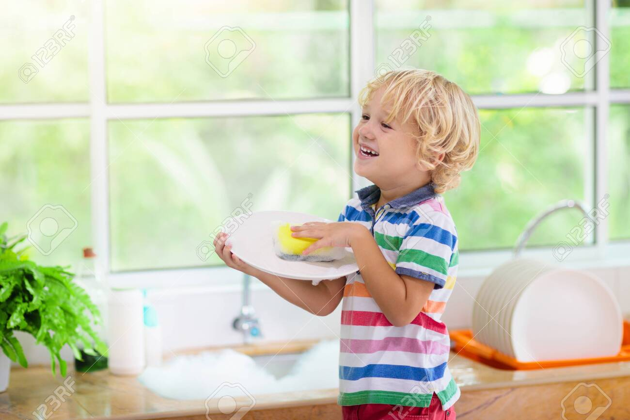 Child washing dishes. Home chores. Kid in white kitchen cleaning plates after lunch at window. - 128867514