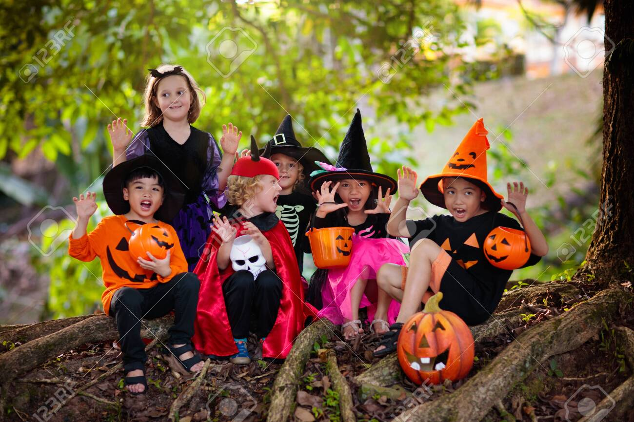 Child in Halloween costume. Mixed race Asian and Caucasian kids trick or treat on suburban street. Little boy and girl with pumpkin lantern and candy bucket. Baby in witch hat. Autumn holiday fun. - 129956240