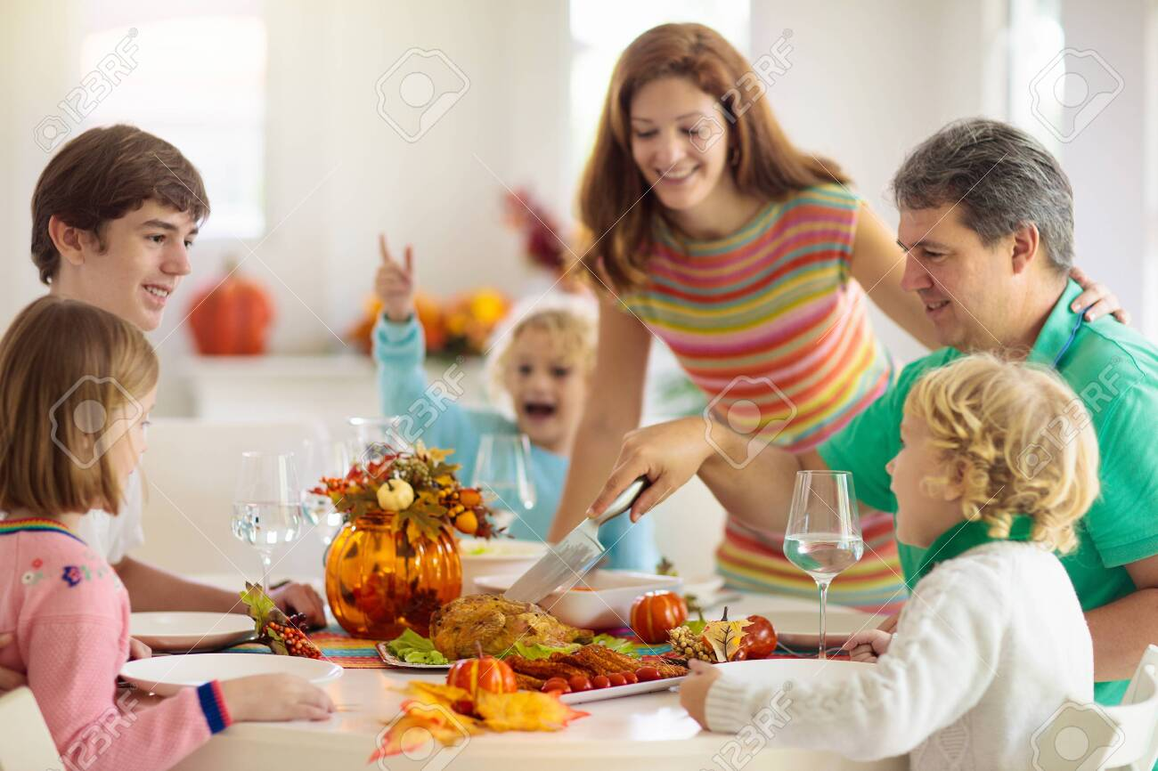 Family with kids eating Thanksgiving dinner. Roasted turkey and pumpkin pie on dining table with autumn decoration. Parents and children having festive meal. Father and mother cutting meat. - 130660663