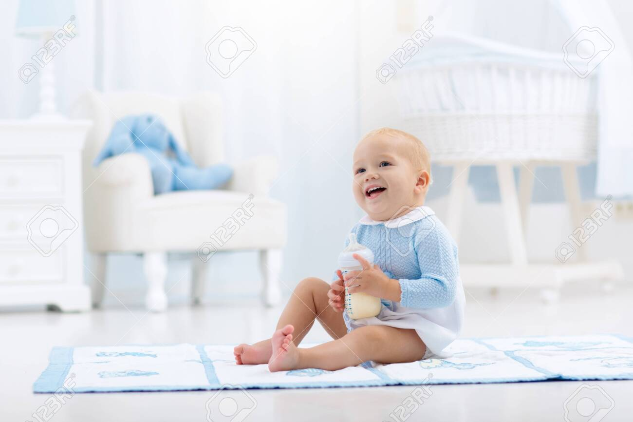 Adorable baby boy playing on a blue floor mat and drinking milk from a bottle in a white sunny nursery with rocking chair and bassinet. Bedroom interior with infant crib. Formula drink for infant. - 131756592