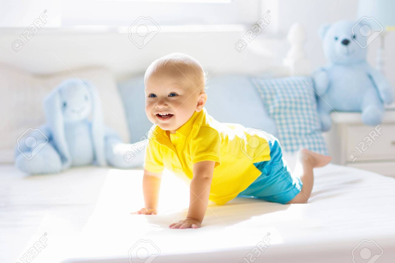Baby playing on parents bed. Cute funny little boy learning to crawl in white sunny nursery. Infant and toddler room interior. Bedding and toys for kids. Children play at home. Baby bedroom. - 131756975