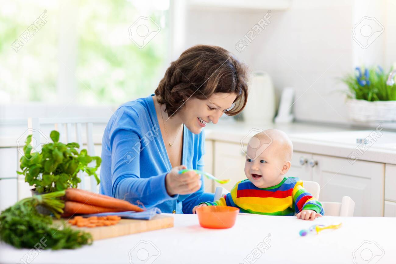 Mother feeding child. First solid food for young kid. Fresh organic carrot for vegetable lunch. Baby weaning. Mom and little boy eat vegetables. Healthy nutrition for children. Parents feed kids. - 134457547