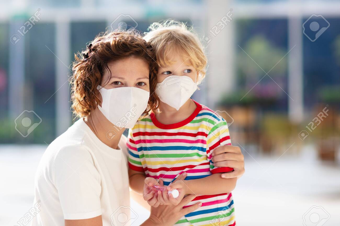 Family with kids in face mask in shopping mall or airport. Mother and child wear facemask during virus and flu outbreak. Virus and illness protection, hand sanitizer in public crowded place. - 140418674