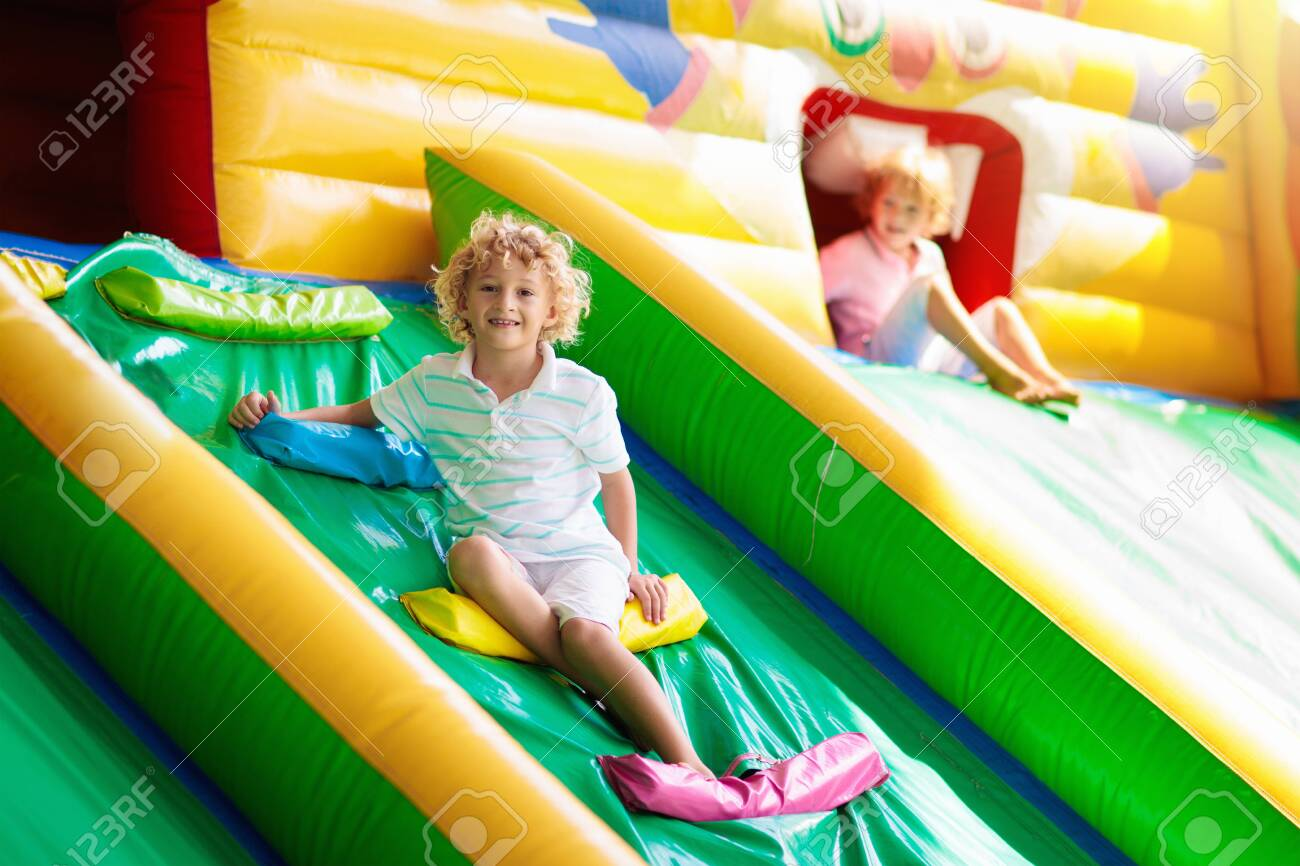 Child jumping on colorful playground trampoline. Kids jump in inflatable bounce castle on kindergarten birthday party Activity and play center for young child. Little boy playing outdoors in summer. - 141336850