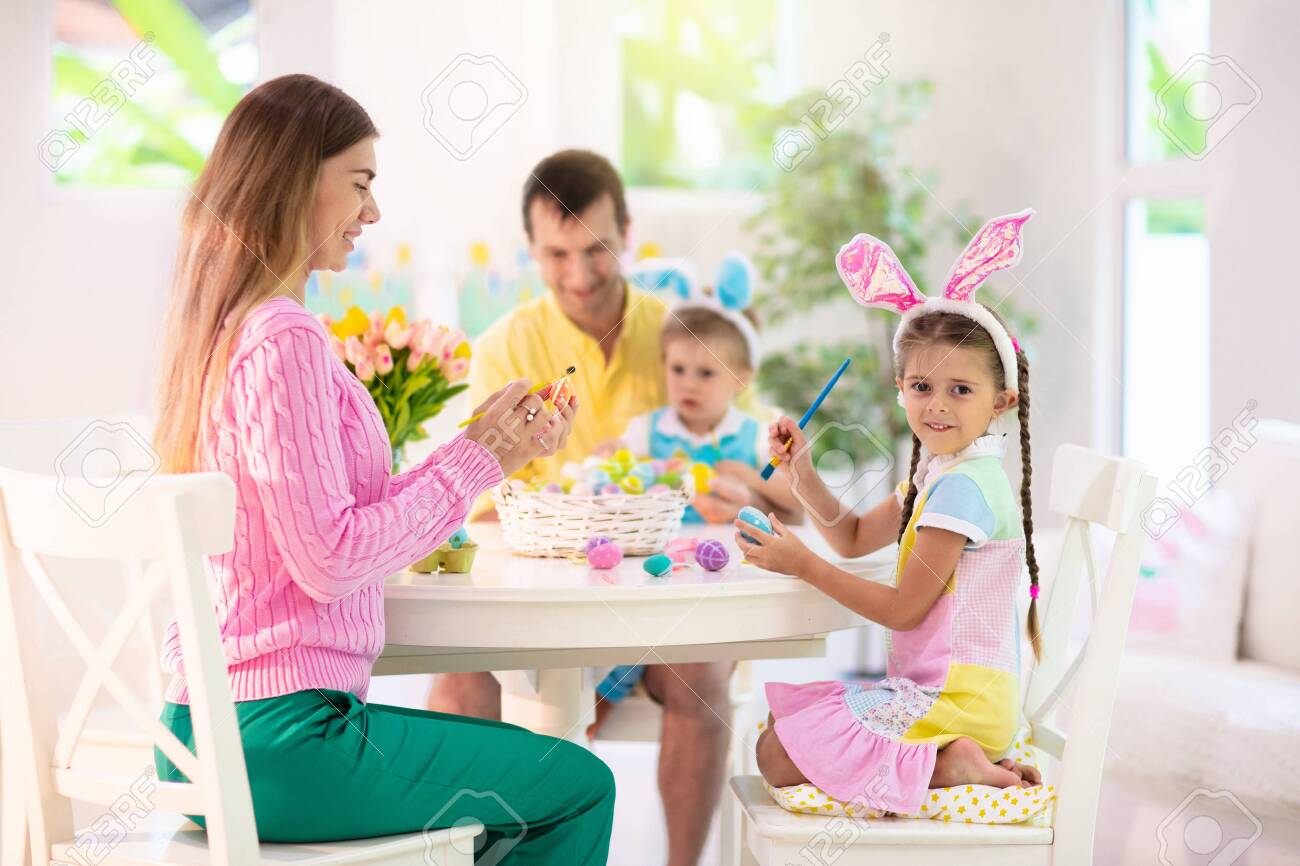 Mother, father and kids color Easter eggs. Mom, dad, little girl and boy with bunny ears dying and painting for Easter egg hunt. Family and child celebration. Home decoration for spring holiday. - 144130968