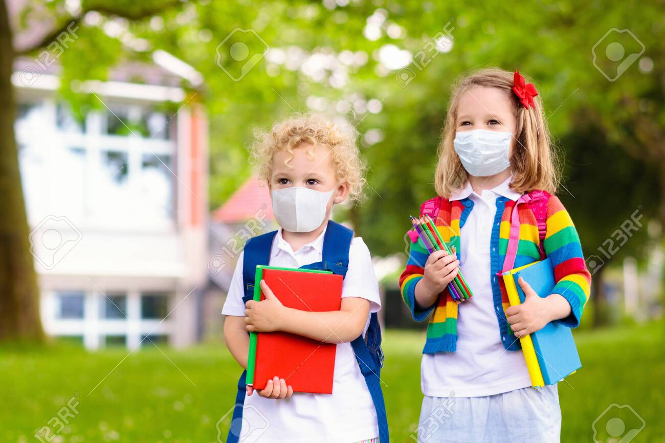 School child wearing face mask during corona virus and flu outbreak. Boy and girl going back to school after covid-19 quarantine and lockdown. Group of kids in masks for coronavirus prevention. - 146540605