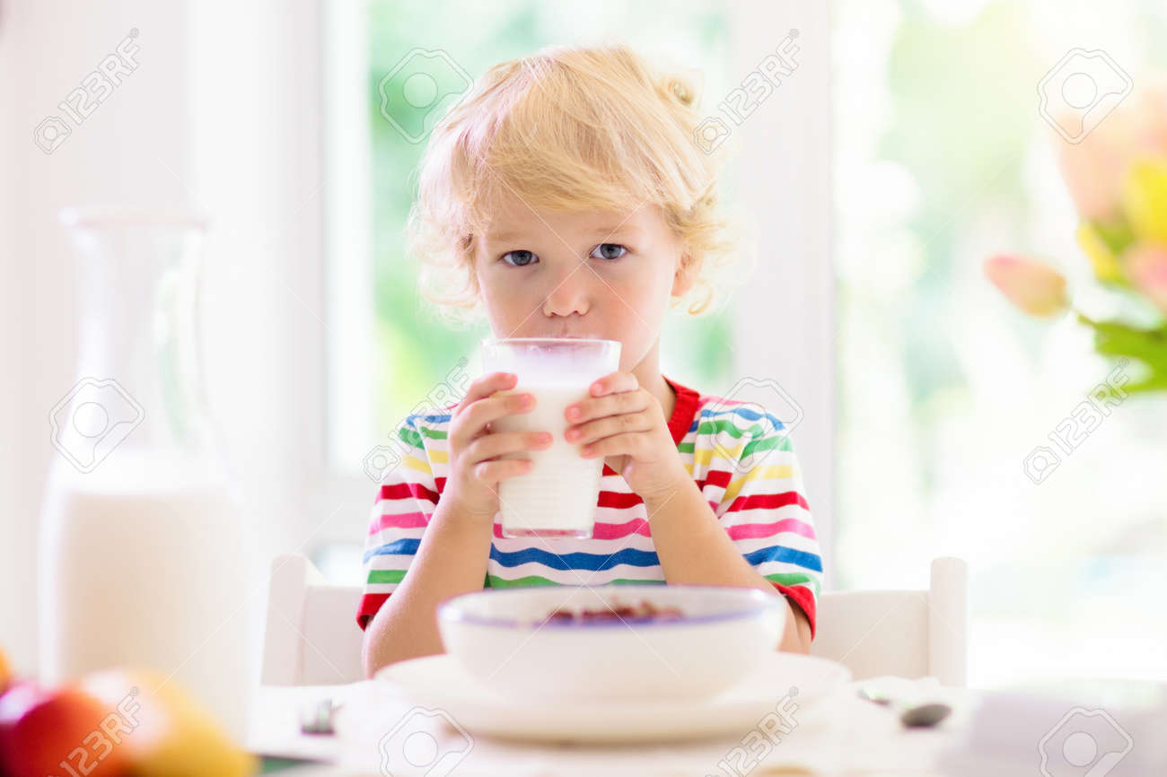 Child having breakfast. Kid drinking milk and eating cereal with fruit. Little boy at white dining table in kitchen at window. Kids eat on sunny morning. Healthy balanced nutrition for young kids. - 154589877
