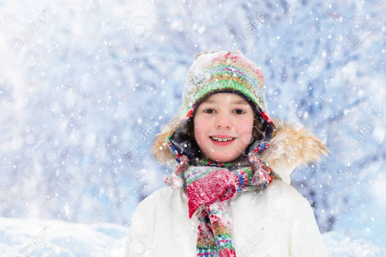 Child playing with snow in winter. Little boy in colorful jacket and knitted hat catching snowflakes in winter park on Christmas. Kids play and jump in snowy forest. Snow ball fight for children. - 157756733